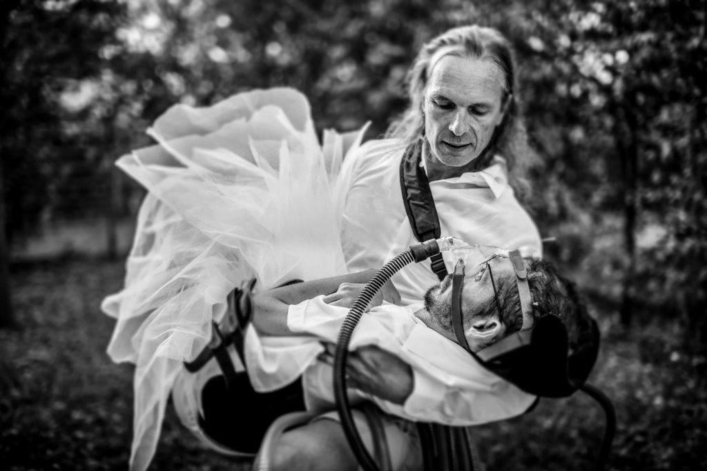 Yann Marussich porte dans ses bras Kamil Guenatri habillé avec un toutou comme s'il s'agissait d'une robe de mariée. On voit en premier plan le tuyau du respirateur dont il ne se sépare jamais.